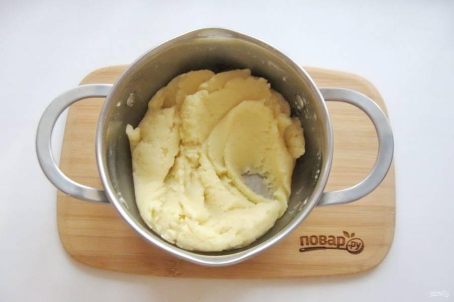 Всыпьте щепотку соли. Когда масло полностью растворится в воде, добавьте муку. Тщательно перемешайте до получения однородной массы, хорошо отходящей от стенок кастрюли.