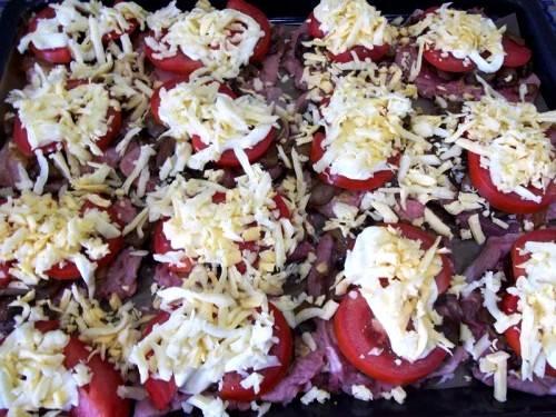 На грибы раскладываем ломтики помидоров, смазываем их майонезом и посыпаем тертым на крупной терке сыром. Ставим противень в разогретую до 200 градусов духовку и запекаем отбивные пол часа. Готовое блюдо можно украсить свежей зеленью и оливками и подать к столу. Приятного аппетита!
