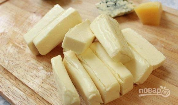 Плавленый сыр достаньте из упаковки и нарежьте крупными брусочками.
