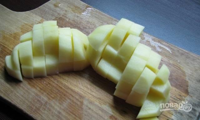 Картофель почистите, помойте и нарежьте кубиками. Поставьте его вариться в подсоленной воде на 15 минут.