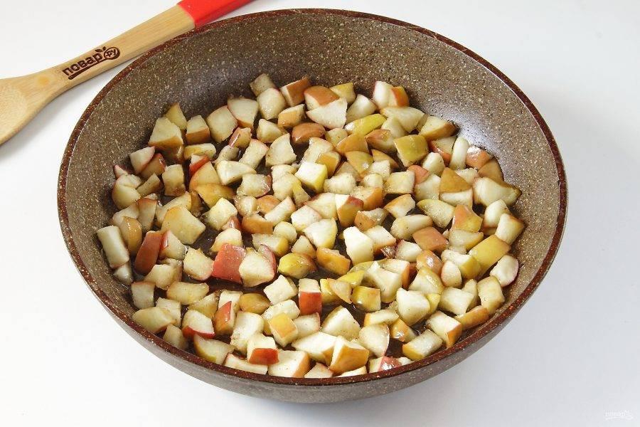 На сковороде разогрейте 50 г сахара и 15 г масла, добавьте яблоки и готовьте их, пока они не карамелизируются.