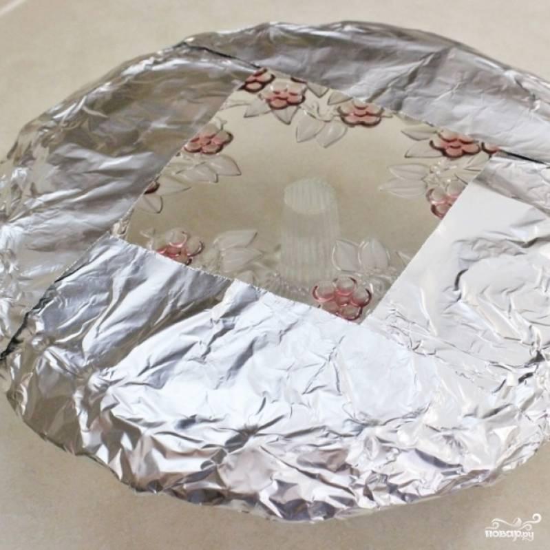 11. Охладите торт в холодильнике. Держите его там как минимум два часа. Лучше всего оставить торт в холодильнике на ночь. Утром (или через пару часов) приготовьте тортовницу на ножке. Края тортовницы затяните фольгой (чтобы ее не испачкать глазурью).