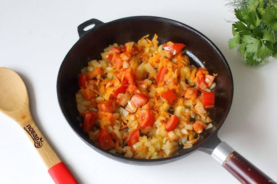В сковороде разогрейте масло и обжарьте до мягкости нарезанный кубиками лук и тертую морковь. Добавьте нарезанный кубиками помидор и готовьте все вместе еще 1-2 минуты.