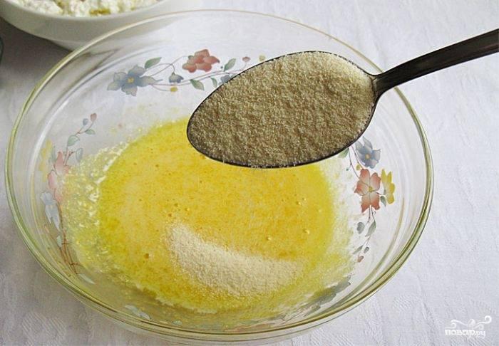 1.В первую очередь отделяем белки от желтков, первые отправляем в холодильник, а вторые кладем в миску, добавляем сахарный песок и взбиваем до растворения. Всыпаем манную крупу и оставляем на 20 минут. Затем смешиваем массу с протертым творогом.