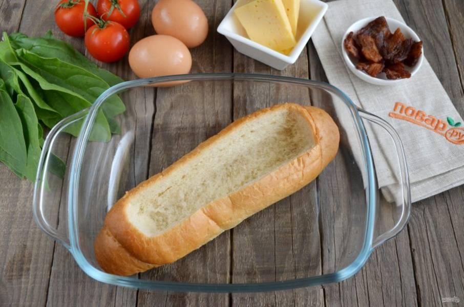 Возьмите булочку и острым ножом вырежьте в ней аккуратное отверстие, чтобы вложить начинку. Серединку удалите руками.