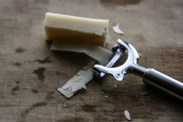 Ножом для сыра нарежьте пару ломтиков пармезана.