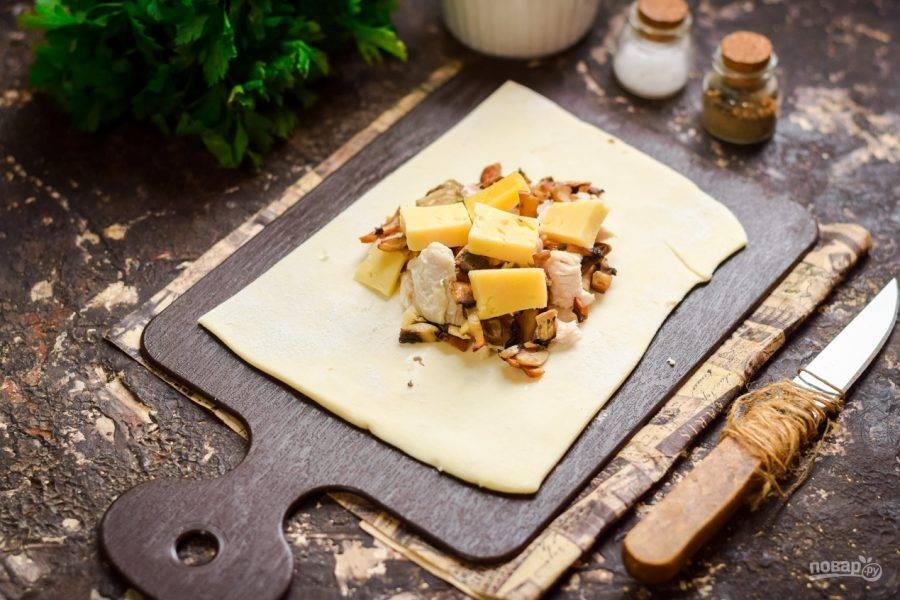 По центру теста выложите немного грибов, вареное куриное филе, кусочки твердого сыра. Соль и перец добавьте по вкусу.