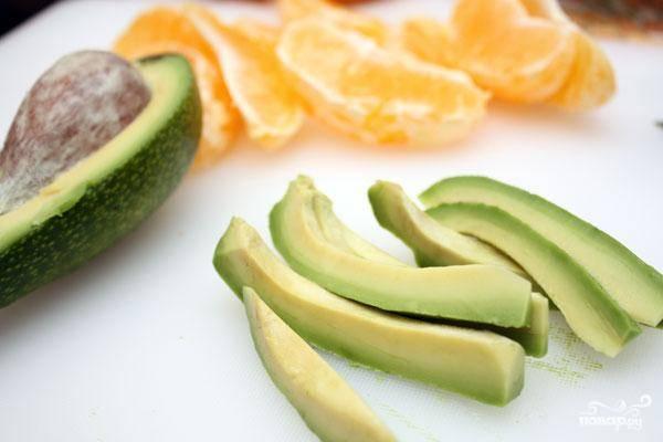 Авокадо очищаем от косточки и кожуры, нарезаем на тонкие и продолговатые брусочки. Апельсин аккуратно разбираем на дольки. И то, и другое выкладываем в салатницу.