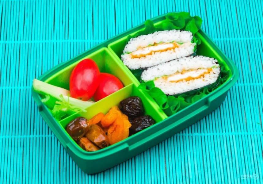 4. Заверните нори в форме конверта и обмотайте пищевой пленкой, чтобы сэндвич хорошо закрепился. Оставьте на некоторое время. Разрежьте сэндвич пополам и выложите в ланч бокс. В качестве дополнения нарежьте овощи. Приятного аппетита!