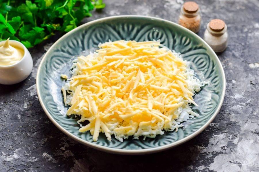 Поверх выложите слой тертого твердого сыра. Также смажьте немного майонезом.