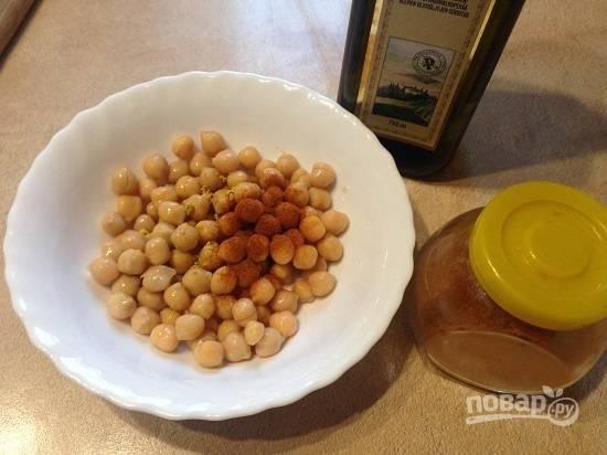 1. Я использую уже готовый консервированный нут. Сливаем жидкость и добавим к зернам столовую ложку растительного масла, паприку, острый молотый перец и имбирь. Хорошо перемешиваем и перекладываем в посуду, в которой можно запекать в духовке.
