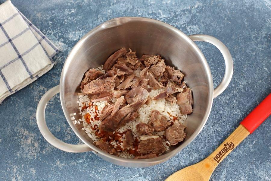 Переложите овощную зажарку в кастрюлю, добавьте промытый рис и нарезанное кусочками мясо.