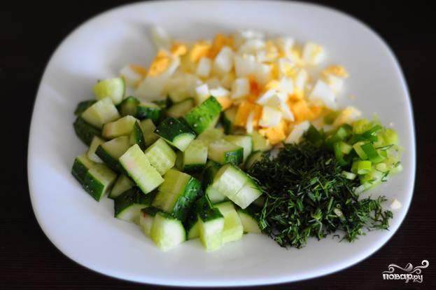 2.Отвариваем яйца, после чего нарезаем их кубиком. Моем и нарезаем свежий огурец кубиком, моем и нарезаем зелень и лук.