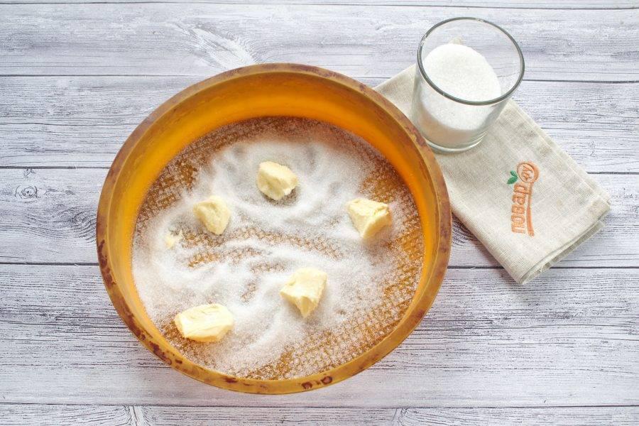 На дно силиконовой формы для запекания насыпьте 1/2 стакана сахара, разложите кусочки сливочного масла. Если используете не силиконовую форму, то постелите на ее дно пергамент для выпечки так, чтобы его концы поднимались над бортиками.