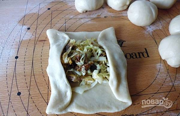 Тесто разделите на 7-8 одинаковых кусочков. Раскатайте каждый кусочек в пласт 0,5 см и выложите начинку из капусты и грибов.