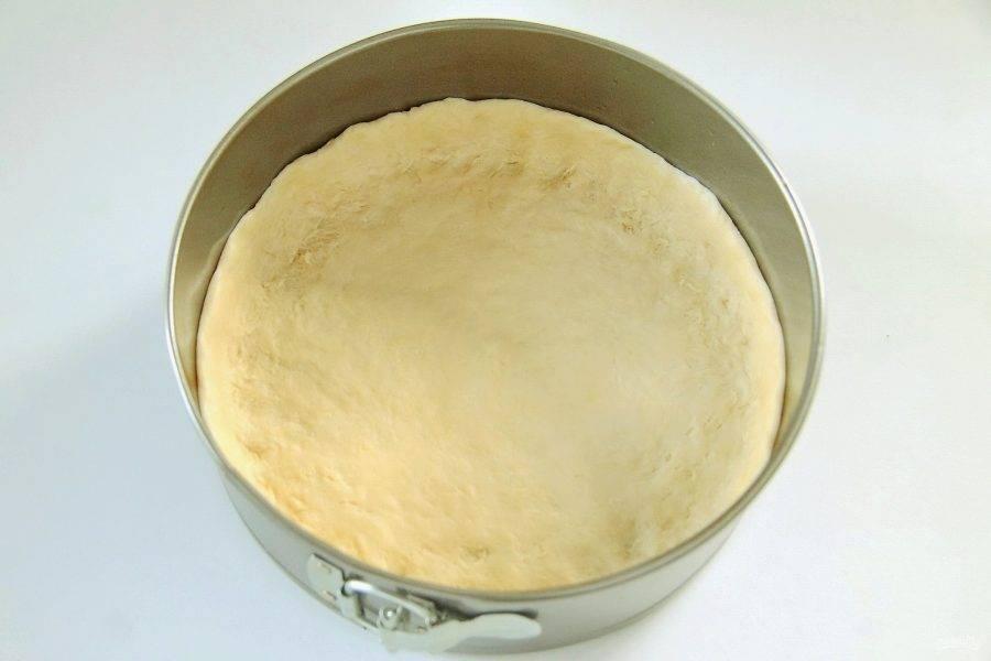 Разделите тесто на две части. Одну часть раскатайте на столе и аккуратно перенесите в смазанную маслом форму для выпечки. Руками сформируйте небольшие бортики.