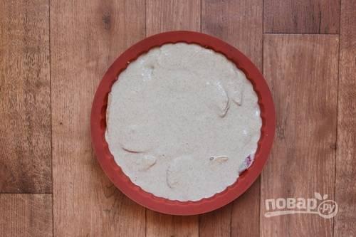 4. Вылейте на дно жаропрочной формы (лучше всего использовать силикон или застелить пергаментом) 1/4 часть теста. Распределите яблоки и сверху вылейте оставшееся тесто. Отправьте форму в разогретую до 180 градусов духовку.