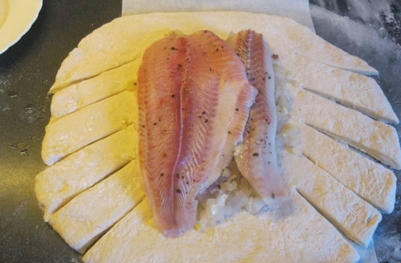 5. По бокам делаем небольшие надрезы (как на фото). В центр выкладываем лук и рыбу.