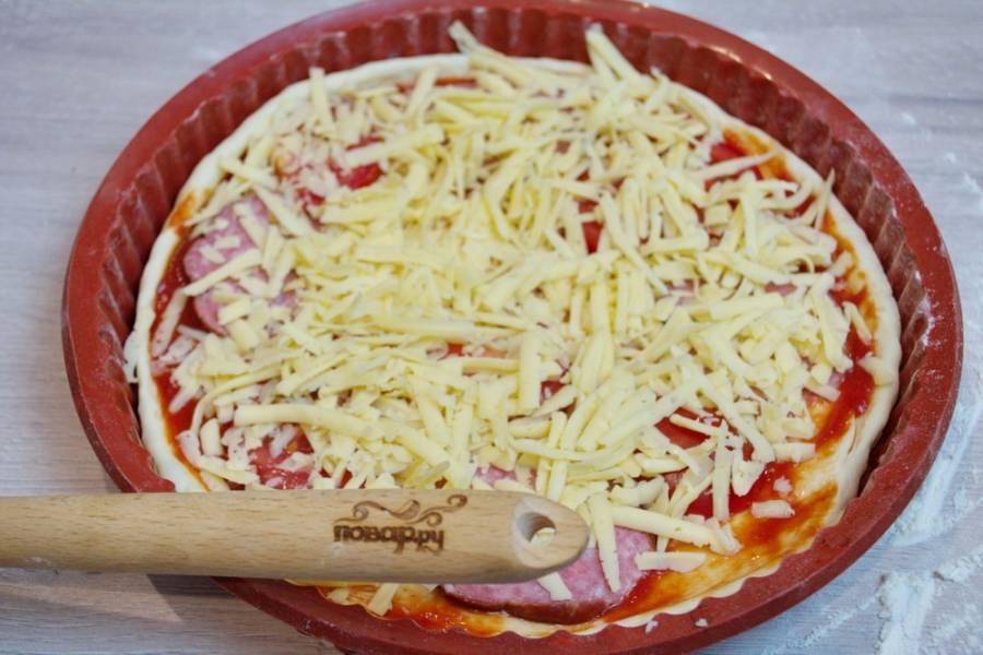 Натрите на крупной терке сыр. Посыпьте сыром всю пиццу. Используйте именно крупную терку, чтобы при запекании сыр не превратился в чипсы.