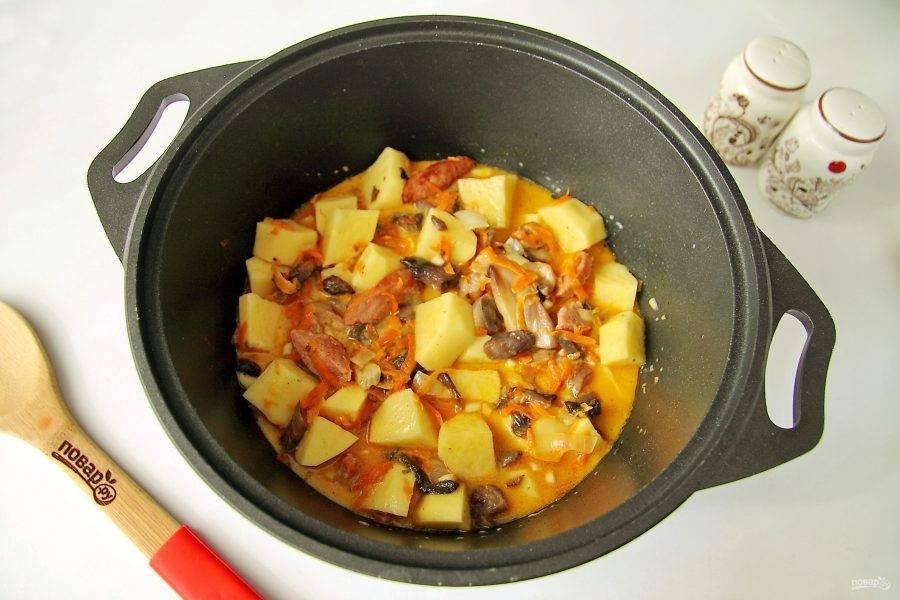 Влейте немного воды и тушите все на небольшом огне до полной готовности картофеля.