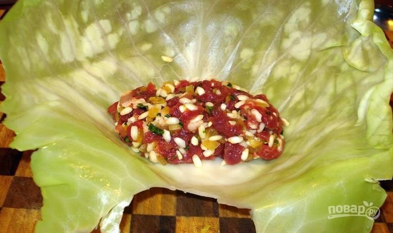 Предварительно кочан капусты нужно отварить в кипящей воде 5-6 минут, чтобы листья размякли. Отделяем один листок и выкладываем на него начинку.
