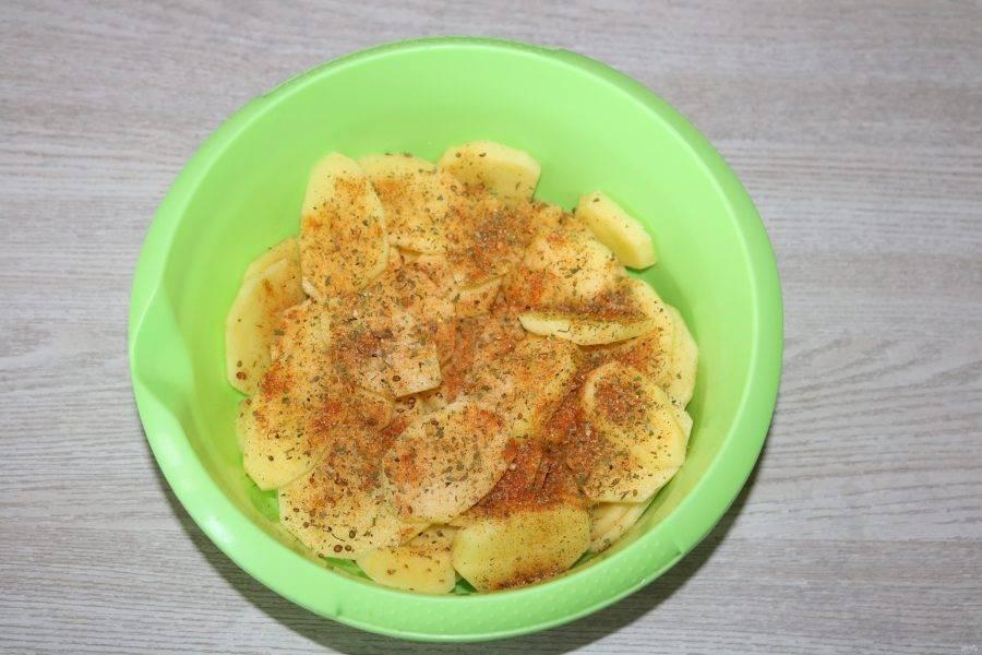 Картофель выложите в миску, посолите, посыпьте специями.