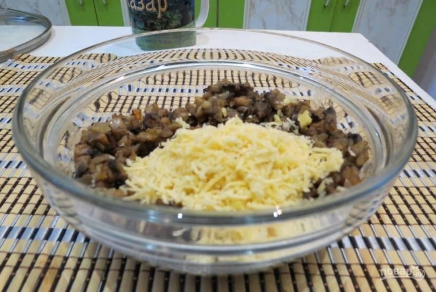 Половину сыра натрите к остывшим грибам с луком.