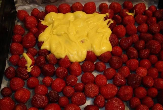 Форму для запекания застелите бумагой, выложите ягоды и аккуратно залейте тестом.