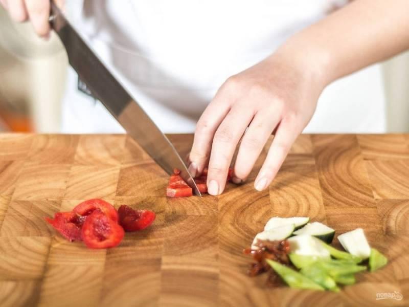Нарежьте средними кусочками перец, горох, цуккини и помидоры. Измельчите чеснок.