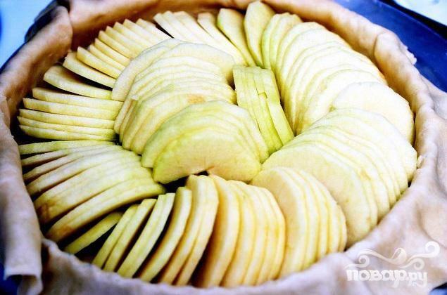 3. Яблоки очистить от кожуры, сердцевины и нарезать ломтиками. Выложить яблоки поверх теста в форме кольца, начиная от края, чтобы ломтики перекрывали друг друга. Оставьте нетронутыми   5 см теста от краев.