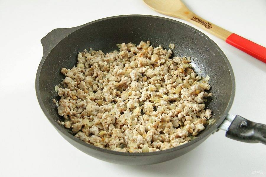 Добавьте к луку фарш, соль и любимые специи. Обжарьте все вместе до полной готовности.