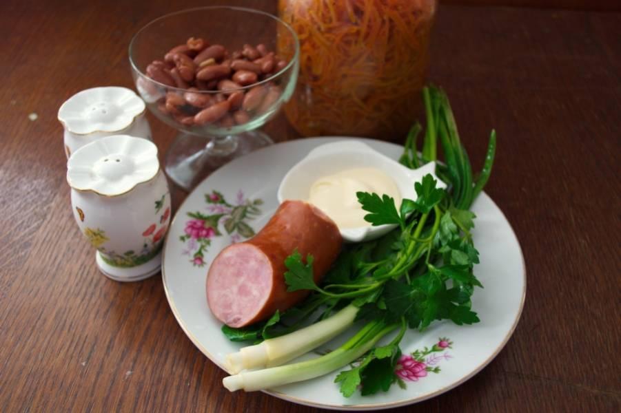1. Для приготовления салата нам необходимы: фасоль красная консервированная в томатном соусе, зеленый лук, петрушка, корейская морковка, колбаса варено-копченая.