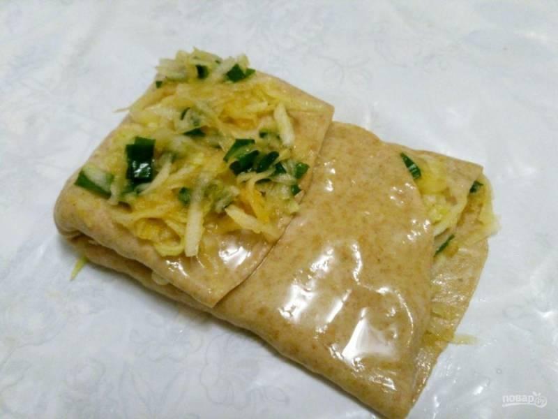 Накройте начинку свободным краем теста, снова смажьте его поверхность маслом и опять положите небольшое количество начинки.