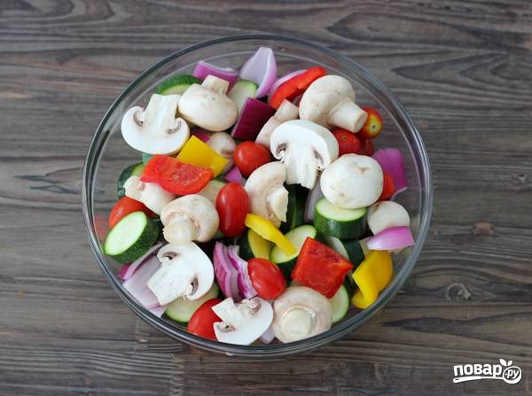 2. Лук и перец нарежьте средними кусочками, кабачки - кружочками, грибы - пополам. Помидоры оставьте целыми. Выложите все в глубокую мисочку.