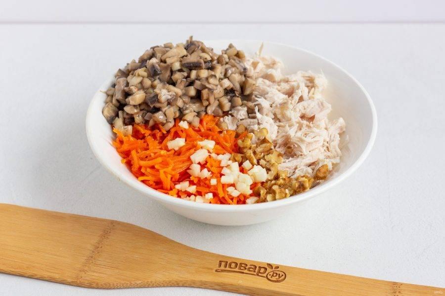 Шампиньоны мелко нарежьте и обжарьте 2-3 минуты в растительном масле, подсолите. В миске соедините нарезанное кубиками филе, обжаренные шампиньоны, рубленную морковь по-корейски и чеснок, также кусочки орехов.