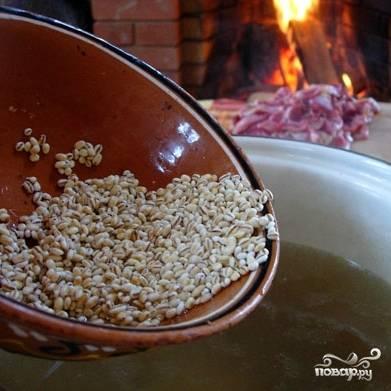 По истечению оговоренного часа приготовления бульона, извлекаем из мясного бульона овощи и мясо. Овощи нам уже не понадобятся вообще, а мясо, при желании, можно будет добавить в суп в самом конце варки. В оставшийся бульон кладем желудки и перловую кашу, варим 20 минут на среднем огне.
