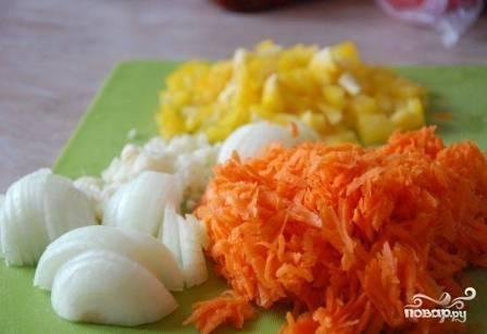 Затем натираем морковь на крупной терке, перец нарезаем небольшими кубиками, лук — кубиками или полукольцами. Чеснок мелко порубим или пропустим через чеснокодавку.