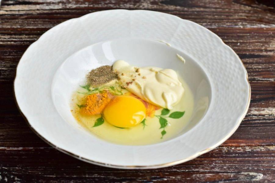 Вбейте куриное яйцо, выложите майонез, всыпьте соль, молотый перец, куркуму, мускатный орех, имбирь. Хорошо все перемешайте вилочкой.