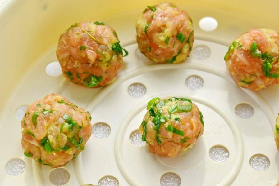 Соедините с рубленым филе лосося, вымесите до однородности. Сформируйте из фарша котлетки в виде шариков, размером с грецкий орех. Поместите рыбные котлетки в чашу для варки на пару, в чашу пароварки. Отварите в течение 10 минут.