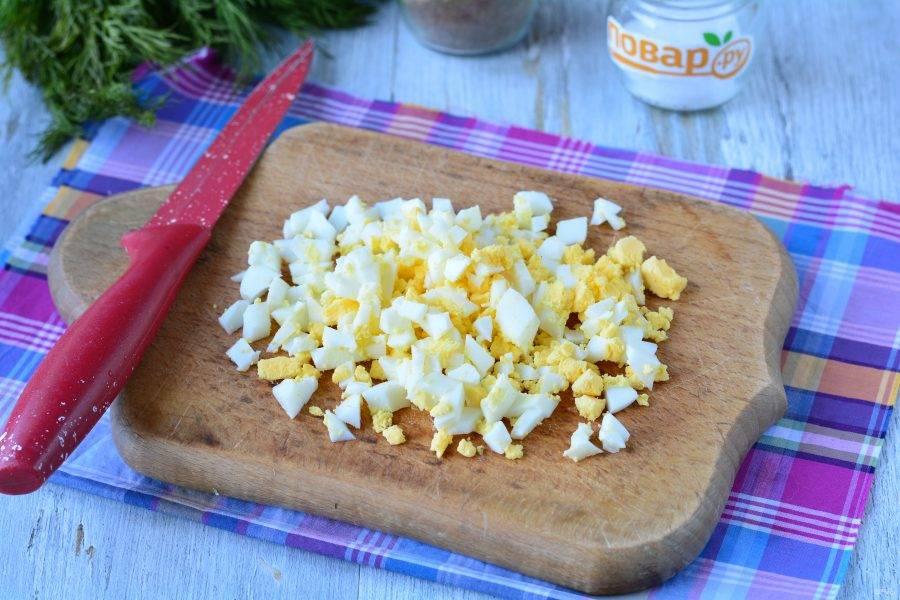 Сварите куриные яйца вкрутую, остудите и нарежьте кубиками.