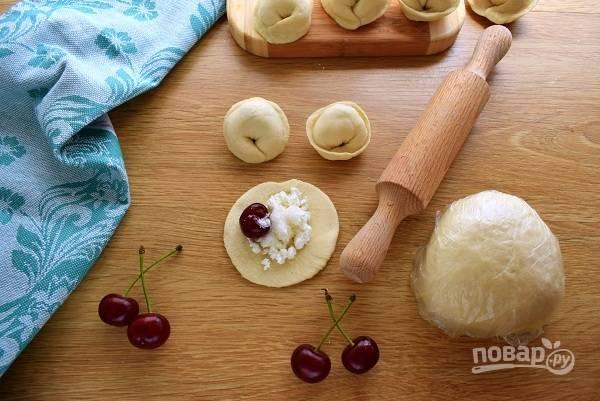 Каждый кусочек раскатайте в тонкую лепешку, в центр которой добавьте сахар, творог и вишенку. Сверните лепешку пополам и  защипните ее края. Затем сведите концы заготовки вместе и тщательно закрепите.