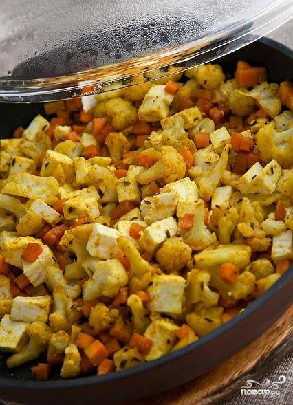 Все овощи и сыр режем мелкими кубиками. Разогреваем сковородку, наливаем в нее масло. Высыпаем кумин, обжариваем его, затем засыпаем все остальные специи. Через несколько секунд высыпаем нарезанные кубиками овощи и сыр. Накрываем крышкой и обжариваем все около 5-7минут.