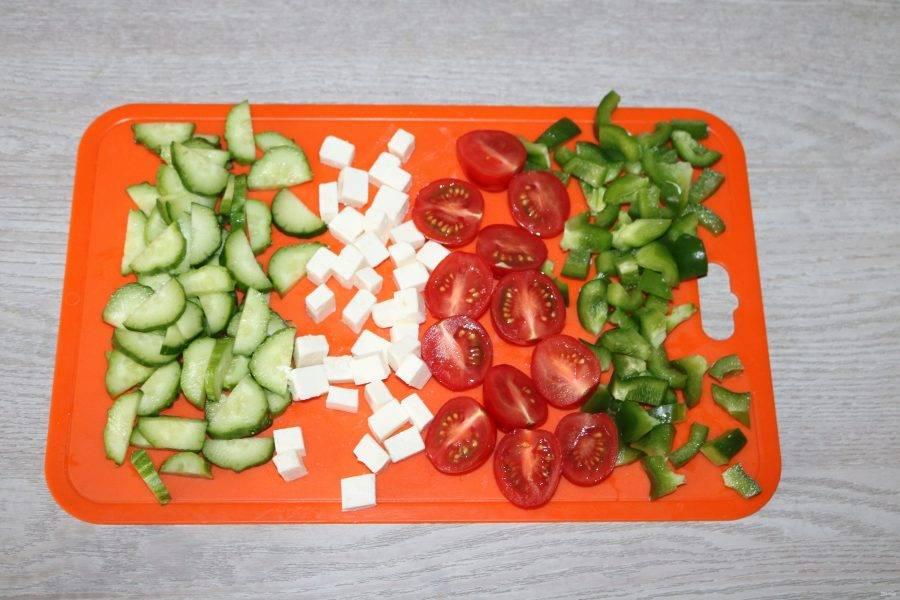 Нарежьте помидоры черри на половинки, перец и сыр кубиками, огурцы полукольцами.