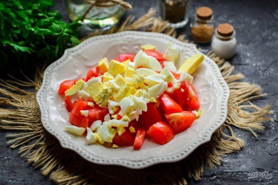 Куриное яйцо отварите 10 минут в подсоленной воде, после остудите и почистите. Нарежьте яйцо небольшими кубиками. Добавьте яйцо к помидорам.