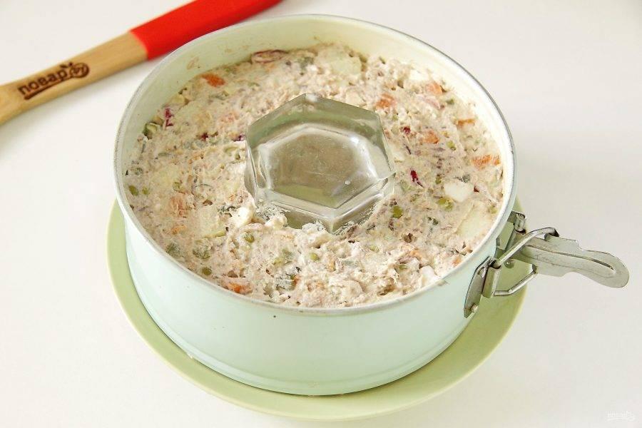 Все хорошо перемешайте и переложите салат на сервировочное блюдо, разместив кулинарное кольцо. У меня кольцо от разъемной формы для выпечки, диаметром 18 см. В центр поставьте стакан. Примните салат сверху лопаткой.