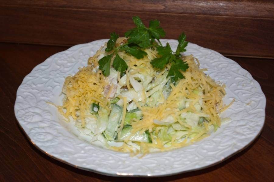 Заправьте салат сметаной. Добавьте специи по вкусу. Выложите салат горкой на тарелку. Посыпьте натертым сыром. Подайте к столу, украсив веточкой петрушки.