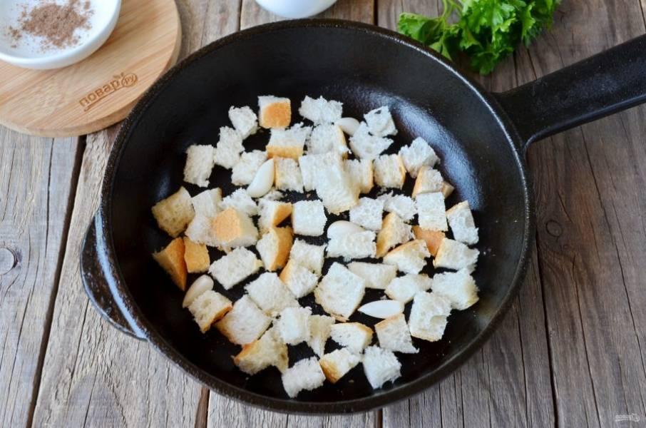5. Пока суп варится, приготовьте сухарики. Для этого порежьте французский багет маленькими кубиками, очистите 4-5 зубчиков чеснока. На сухой сковороде обжаривайте хлеб с чесноком до характерного вида и вкуса. Отставьте сковороду.