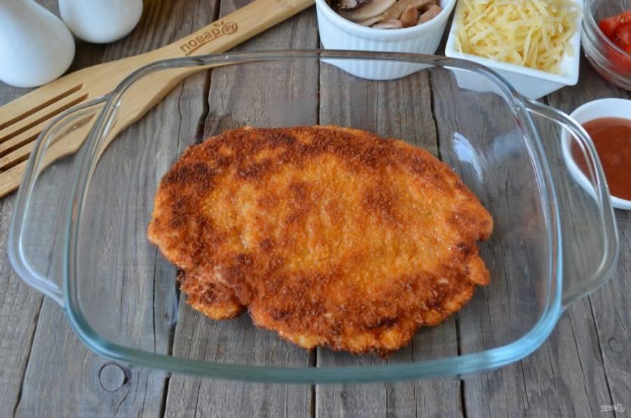 Куриное филе обжарьте в большом количестве масла с двух сторон до готовности. Положите его в огнеупорную форму для запекания.