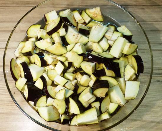 Шаг первый. Для начала займемся баклажаном. Не снимая кожуры порубим его на кусочки среднего размера и замочим в соленной воде (где-то 1-2 столовых ложки на 1,5 литра). Это уберет из плода горечь.