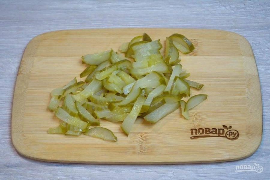 3. Соленые огурчики нарежьте соломкой. Можно все продукты салата нарезать кубиком, тогда вид салата будет немного другой.